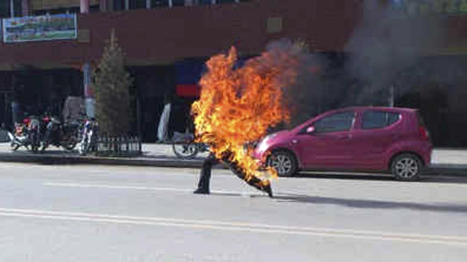 FILE - In this Oct. 23, 2012 file photo released by London-based rights group Freetibet.org, Dorje Rinchen, a farmer in his late 50s, runs after setting himself on fire on the main street in Xiahe, in northwestern China's Gansu province. Chinese authorities are responding to an intensified wave of Tibetan self-immolation protests against Chinese rule by clamping down even harder — criminalizing the suicides, arresting protesters' friends and even confiscating thousands of satellite TV dishes. (AP Photo/Freetibet.org, File) EDITORIAL USE ONLY, NO SALES