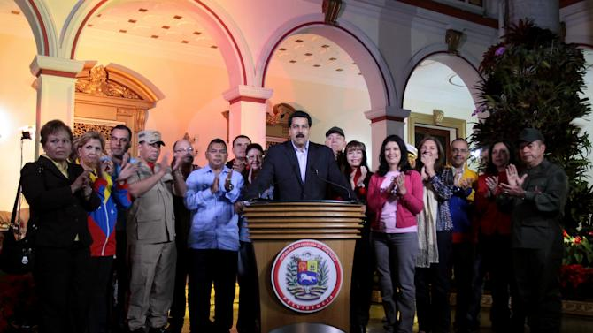 """In this photo released by Miraflores Press Office, Venezuela's Vice-President Nicolas Maduro, center, accompanied by other members of the cabinet, delivers a speech at the presidential palace in Caracas, Venezuela, Tuesday, Dec. 11, 2012. Maduro said on Venezuelan television Chavez was recovering in Cuba after an operation targeting an aggressive cancer that has defied multiple treatments. The operation was """"complex"""" but was completed """"correctly and successfully,"""" he said. (AP Photo/Miraflores Press Office, Francisco Batista)"""
