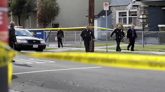 Los Angeles Police Department officers and investigators work at the scene of a shooting of two USC students in Los Angeles on Wednesday, April 11, 2012. Police said a gunman opened fire on a BMW near the University of Southern California campus on Wednesday, killing two international students from China in what may have been a bungled carjacking attempt.  (AP Photo Damian Dovarganes)