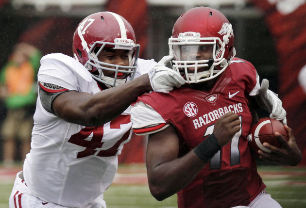 Arkansas quarterback Brandon Mitchell, right, carries against Alabama linebacker Xzavier Dickson (47) during the first quarter of an NCAA college football game in Fayetteville, Ark., Saturday, Sept. 15, 2012. (AP Photo/Danny Johnston)
