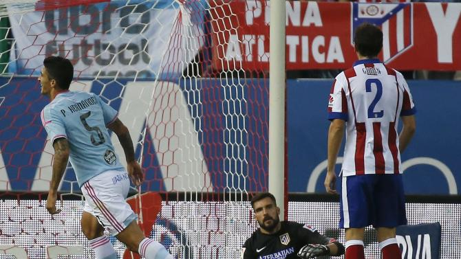 Celta Vigo's Hernandez celebrates his goal in front of Atletico Madrid's goalkeeper Moya and Atletico Madrid's Godin during their Spanish first division soccer match at Vicente Calderon stadium in Madrid