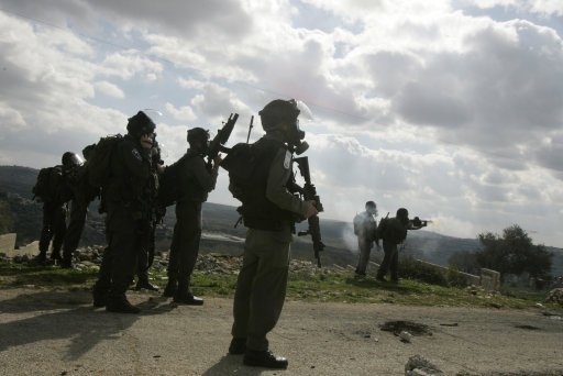 Israeli border officers fires tear gas towards Palestinian demonstrators during a protest in the village of Kufr Qaddum, near the Israeli settlement of Kdumim, in the northern West Bank, Friday, Jan. 20, 2012. (AP Photo/Nasser Ishtayeh)