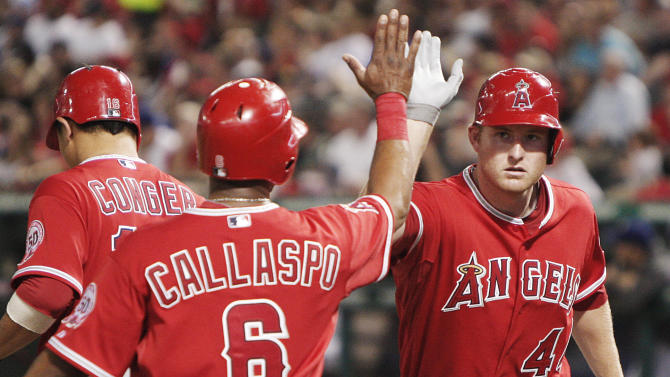 Los Angeles Angels' Mark Trumbo (44) is congratulated by teammate Alberto Callaspo (6) after scoring a run against the Texas Rangers in the fourth inning during a baseball game Tuesday April. 19, 2011, in Arlington, Texas. (AP Photo/Brandon Wade)