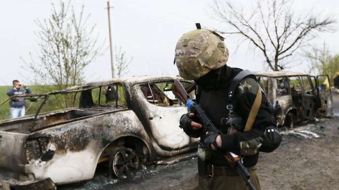 Pro-Russian militant walks past burnt cars near a checkpoint that was the scene of a gunfight overnight near the city of Slaviansk