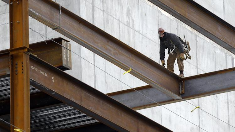 In this Tuesday, April 29, 2014 photo, a worker positions iron girders at a building construction site, in Boston. The Labor Department releases first-quarter productivity data on Wednesday, May 7, 2014. (AP Photo/Steven Senne)