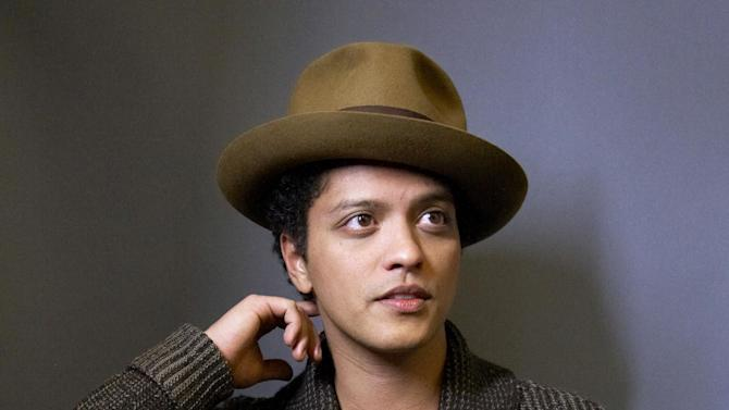 """FILE - This Nov. 5, 2012 file photo shows American singer-songwriter Bruno Mars posing for a portrait in New York. Mars is releasing his sophomore album, """"Unorthodox Jukebox,"""" featuring Grammy-winning jazz singer Esperanza Spalding and production and songwriting work by Mark Ronson, Jeff Bhasker, Diplo, Paul Epworth, Emile Haynie and the Smeezingtons, the production trio that includes Mars, Philip Lawrence and Ari Levine. (Photo by Dan Hallman/Invision/AP, file)"""