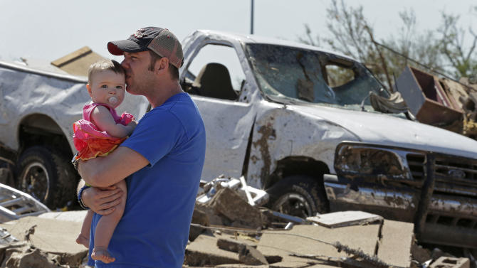 Nick Balen holds his daughter Kinley while visiting the destroyed doctor's office where his wife  worked and survived Monday's tornado, along with 13 other people, Wednesday, May 22, 2013, in Moore, Okla. Cleanup continues two days after a huge tornado roared through the Oklahoma City suburb, flattening a wide swath of homes and businesses. (AP Photo/Charlie Riedel)