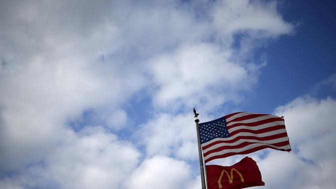 A U.S. flag and a McDonald's logo flag are seen outside one of its restaurants in Joliet