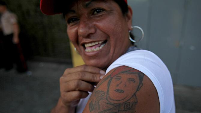 A woman shows a tattoo depicting Venezuela's President Hugo Chavez during a celebration marking his return to his country at Bolivar square in Caracas, Venezuela, Monday, Feb. 18, 2013. Chavez returned to Venezuela early Monday after more than two months of treatment in Cuba following cancer surgery, his government said, triggering street celebrations by supporters who welcomed him home while he remained out of sight at Caracas' military hospital. (AP Photo/Fernando Llano)