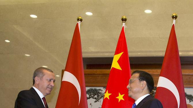 Turkey's President Recep Tayyip Erdogan shakes hands with Chinese Premier Li Keqiang at the Great Hall of the People in Beijing,