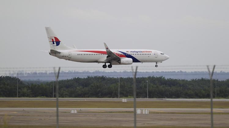 A Malaysia Airlines plane approaches to land at Kuala Lumpur International Airport in Sepang, Malaysia, Friday, Aug. 29, 2014. Malaysia Airlines will cut 6,000 workers as part of an overhaul announced Friday to revive its damaged brand after being hit by double passenger jet disasters. (AP Photo/Lai Seng Sin)