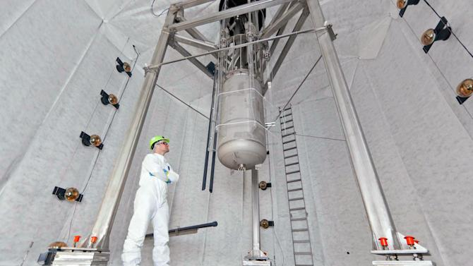 In this Oct. 16, 2012 photo provided by Sanford Lab University of California, Davis, physicist Jeremy Mock inspects the Large Underground Xenon experiment detector, cylinder at center, that has now been lowered into its 70,000-gallon home in a water tank a mile beneath the earth's surface in a shuttered gold mine in Lead, S.D.  The experiment, known as LUX, could begin collecting data on dark matter as early as February _ and, if all goes as planned, that data could answer age-old questions about the universe and its origins, scientists said Monday, Nov. 19, 2012. (AP Photo/Courtesy Sanford Lab, Matt Kapust)