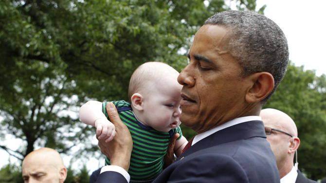 President Barack Obama picks up 4-month-old Parker Cornell of Hubert, N.C., while visiting Section 60 on Memorial Day at Arlington National Cemetery in Arlington, Va., Monday, May 27, 2013. (AP Photo/Molly Riley)