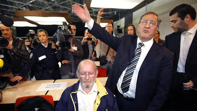 Jean-Claude Mas, center, who founded and ran implant-maker Poly Implant Prothese, attends the opening of his trial at the Parc Chanot temporary courthouse in Marseille, southern France, while his lawyer Yves Haddad gestures to photographers, Wednesday, April 17, 2013.  Some hundreds of women who received faulty breast implants are gathering in the south of France to witness the fraud trial of five executives accused of using cheap industrial silicone to fill tens of thousands of implants around the world.  The now-defunct company exported to more than 60 countries and was one of the world's leading implant makers. (AP Photo/Claude Paris)