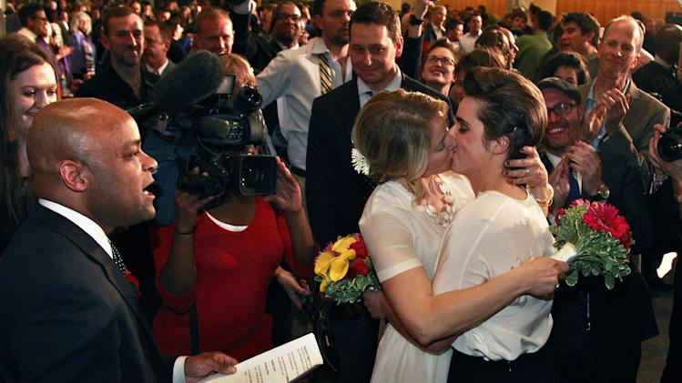Just after midnight, Denver Mayor Michael Hancock, left, performs a civil union vows ceremony for Sonja Semion, center left, and her partner Courtney Law at the Webb Municipal Building in Denver, Wednesday May 1, 2013. In March 2013, the Colorado General Assembly passed SB-11, the Colorado Civil Union Act, which provides committed same-sex couples with legal protections and responsibilities. The act went into effect on May 1, 2013. (AP Photo/Brennan Linsley)