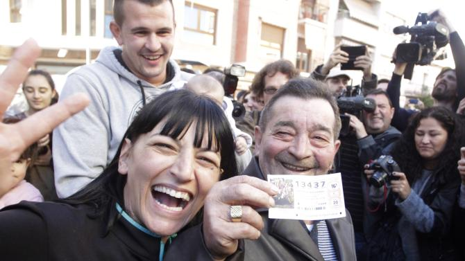 """Juan Lopez holds his lottery ticket with the winning number of Spain's Christmas Lottery """"El Gordo"""", together with his daughter Pilar in La Eliana near Valencia"""