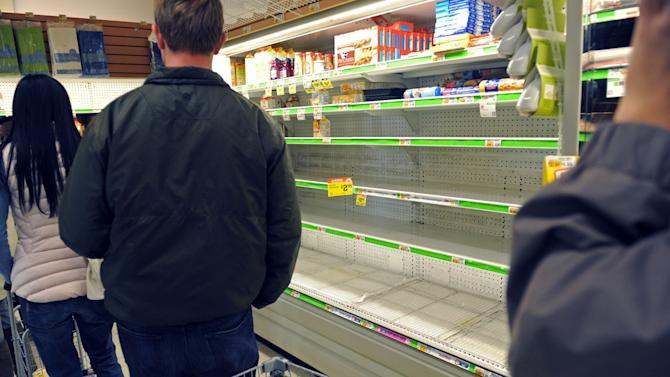 Shoppers pass an empty egg section of a Food Emporium supermarket in the West Village in the wake of the storm, Sunday, Oct. 28, 2012, in New York. Tens of thousands of people were ordered to evacuate coastal areas Sunday as big cities and small towns across the U.S. Northeast braced for the onslaught of a superstorm threatening some 60 million people along the most heavily populated corridor in the nation. (AP Photo/ Louis Lanzano)