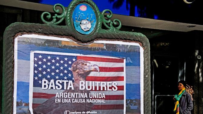 """A woman passes by posters on a wall against the """"vulture funds"""" in Buenos Aires on June 18, 2014"""