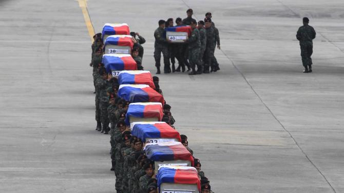 Members of the PNP Special Action Force unit carry metal caskets containing the bodies of slain SAF police who were killed in Sunday's clash with Muslim rebels, upon arriving at Villamor Air Base in Pasay city