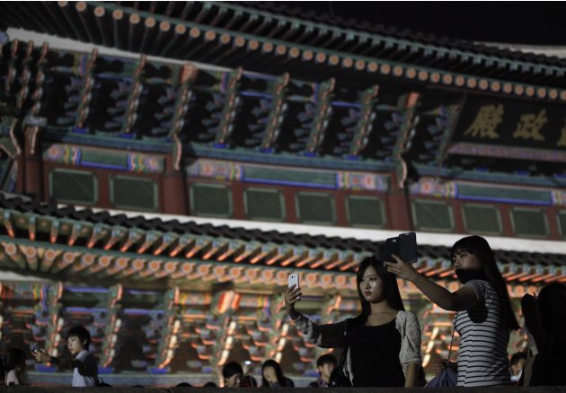 Women take a photograph during the evening at Gyeongbok palace in central Seoul