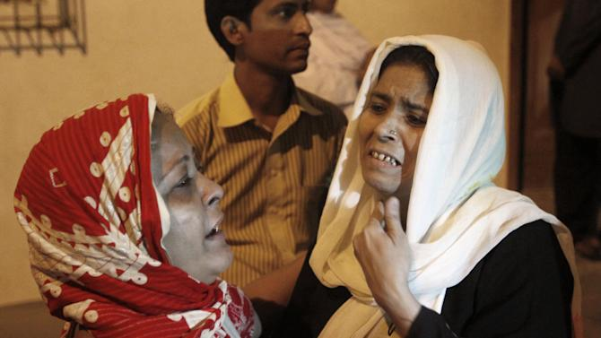 In this Wednesday, March 13, 2013, photo, friends of of Pakistani activist Perween Rahman, who was shot by gunmen on Wednesday night, mourn her death, at a hospital in Karachi, Pakistan. A police official says gunmen have shot and killed a pioneering Pakistani activist who worked in some of the poorest neighborhoods of the country's largest city. (AP Photo/Shakil Adil)