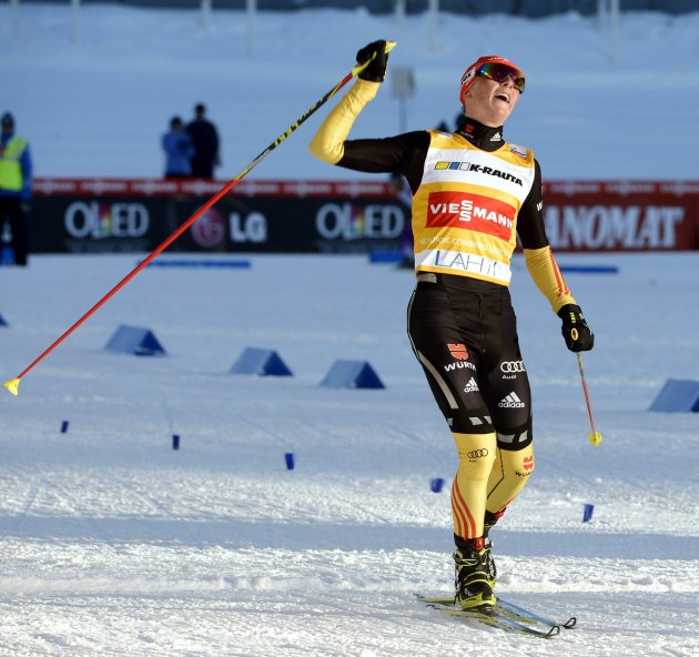 Germany's Eric Frenzel celebrates as he crosses the finish line to win first place during the Nordic Combined individual Gundersen 10 km cross country skiing race at the FIS World Cup Lahti Ski Games