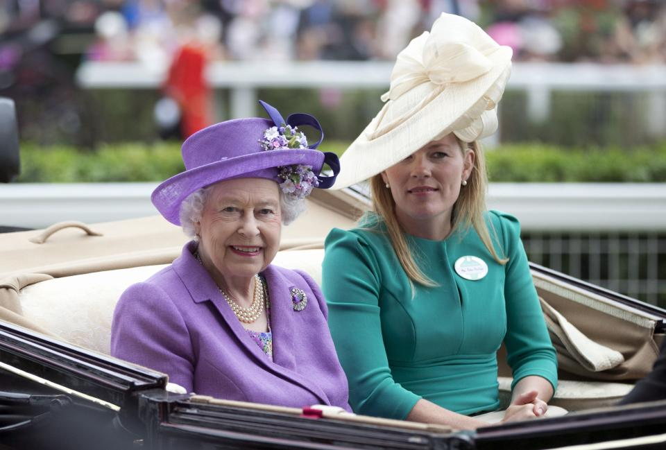 Britain's Queen Elizabeth II arrives by carriage with Autumn Phillips on the third day traditionally known as Ladies' Day of the Royal Ascot horse race meeting, in Ascot, England, Thursday, June 20, 2013. (AP Photo/Alastair Grant)