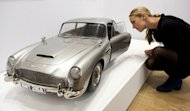 "A Christie's employee poses next to a 1/3 scale replica Aston Martin DB5 used in the new James Bond film ""Skyfall."" Props, costumes and memorabilia from 50 years of Bond films went up for auction in London on Friday, with an Aston Martin car and a pair of Daniel Craig's swimming trunks among the lots"