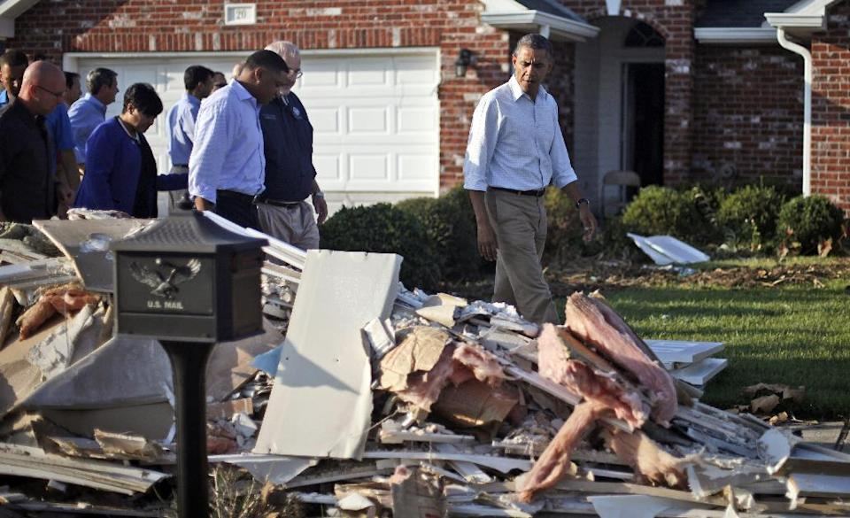 President Barack Obama walks past debris on the sidewalks as he tours the Bridgewood neighborhood in LaPlace, La., in Saint John the Baptist Parish, with local officials to survey the ongoing response and recovery efforts to Hurricane Isaac, Monday, Sept. 3, 2012. (AP Photo/Pablo Martinez Monsivais)
