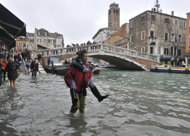 People walk in high water near the Ponte delle Guglie in Venice, Italy, Thursday, Nov. 1, 2012. High tides have flooded Venice, leading Venetians and tourists to don high boots and use wooden walkways