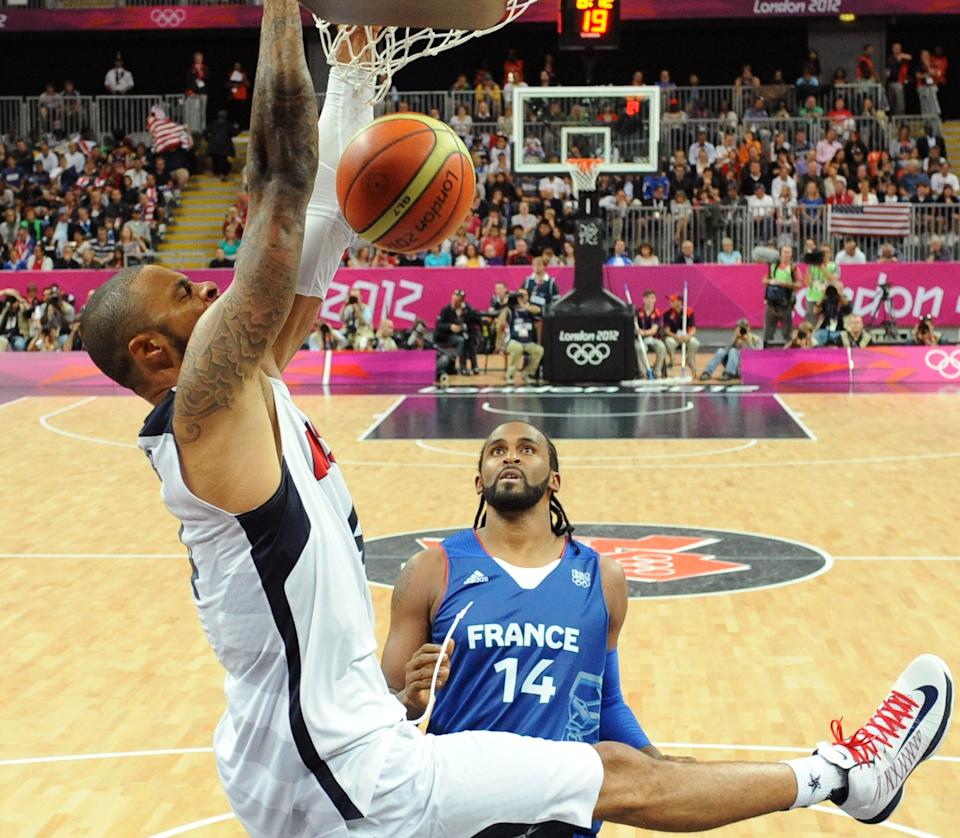 United States' center Tyson Chandler, left, hangs on the hoop in front of French center Ronny Turiaf during the men's basketball preliminary round group A match between the United States and France at the 2012 Summer Olympics, on Sunday, July 29, 2012 in London.  (AP Photo/Mark Ralston, Pool)
