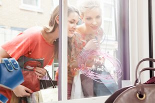 two women shopping window display luxury bag