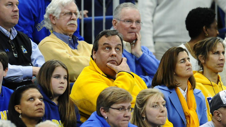 New Jersey Gov. Chris Christie, center, watches the first half of a regional semifinal between Delaware and Kentucky in the NCAA college basketball tournament in Bridgeport, Conn., Saturday, March 30, 2013. (AP Photo/Jessica Hill)