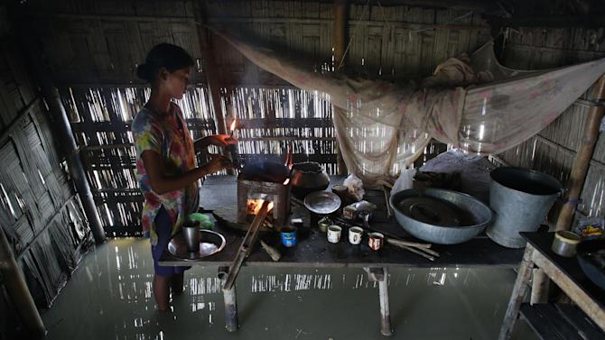 Dupura Akhtar cooks inside her flood-affected house in Ashigarh village, about 70 kilometers (44 miles) east of Gauhati, India, Tuesday, Aug. 19, 2014. Heavy rainfall for the past few days has affected several districts of Assam state, flooding dozens of villages and displacing thousands. (AP Photo/Anupam Nath)