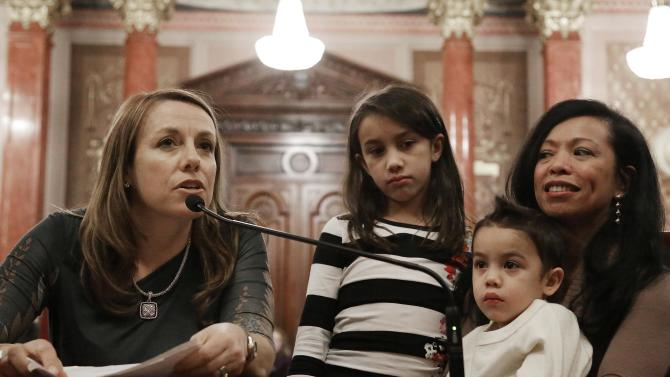 Theresa Volpe, left, testifies along side of her daughter Ava as her partner Mercedes Santos sits with their son Jaidon during a Senate Executive committee hearing considering same sex marriage at the Illinois State Capitol Thursday, Jan. 3, 2013 in Springfield, Ill. (AP Photo/Seth Perlman)