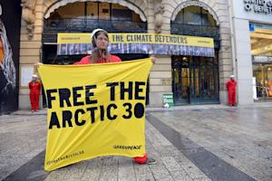 Greenpeace activists stand in front of the Paris headquarters …