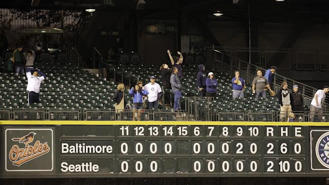 Fans stretch during the 14th inning of a baseball game between Baltimore Orioles and the Seattle Mariners, Tuesday, Sept. 18, 2012, in Seattle. (AP Photo/Ted S. Warren)