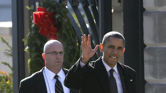President Barack Obama, accompanied by a U.S. Secret Service agent, waves at reporters shouting questions at him regarding the fiscal cliff as he walks from the White House across Pennsylvania Avenue to Blair House in Washington, Thursday, Dec. 13, 2012, to attend a holiday party for the National Security Council. (AP Photo/Charles Dharapak)