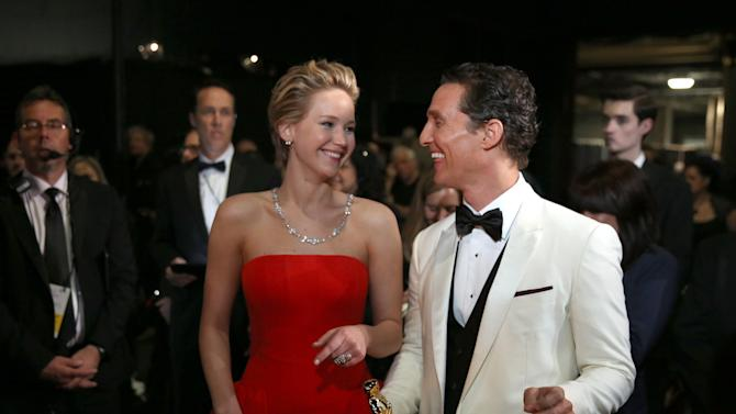 """FILE - In this March 2, 2014 file photo, Jennifer Lawrence, left, and Matthew McConaughey appear backstage during the Oscars at the Dolby Theatre in Los Angeles. Oscar winner """"12 Years a Slave"""" will face off with blockbusters like """"The Hunger Games: Catching Fire"""" and """"The Hobbit: The Desolation of Smaug"""" at the MTV Movie Awards. The network announced Thursday, March 6, 2014, the nominees for its 24th annual Movie Awards. The other movie-of-the-year nominees are """"The Wolf of Wall Street"""" and """"American Hustle."""" Most of the best male and female nominees reassemble recent Oscar contenders like Matthew McConaughey, Lupita Nyong'o and Leonardo DiCaprio. (Photo by Matt Sayles/Invision/AP)"""