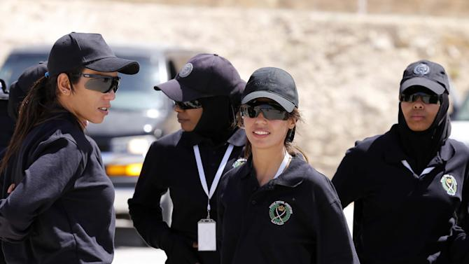 Members of the Jordanian women's police special operations team wait to compete during the 7th Annual International Warrior Competition hosted by the King Abdullah Special Operations Training Center (KASOTC), Sunday, April 19, 2015, Amman, Jordan.  Jordan is hosting a competition of elite anti-terrorism squads from 18 countries, including fellow members of the military coalitions fighting rebels in Yemen and Islamic State extremists in Iraq and Syria. The competition opened Sunday with a drill by Jordanian special forces rescuing hostages from a plane and rappelling from a helicopter. (AP Photo/Raad Adayleh)