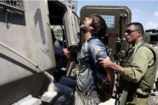 Israeli soldiers detain foreign activists as Palestinian farmers accompanied by foreign and Israeli activists  tried to reach Palestinian farms in the West Bank village of Beit Omar, near Hebron and the Jewish settlement of Karmei Tzur, Saturday, Sept. 10, 2011. Israeli soldiers prevented the group from reaching the farmland. (AP Photo/Nasser Shiyoukhi)