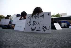 Family members of victims onboard sunken ferry Sewol sit in front of a building in which crew members are detained, after attending a hearing at the local court in Gwangju