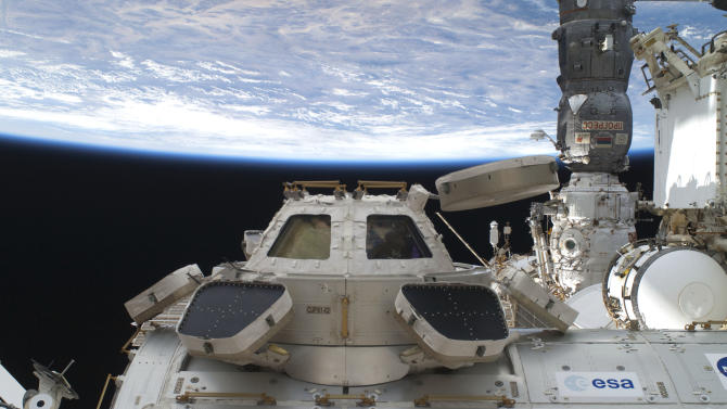 """This image provided by NASA shows a high angle view of the Cupola, backdropped against the darkness of space and Earth's horizon, and some components of the International Space Station. The astronauts making NASA's last shuttle flight turned into moving men and garbage haulers Wednesday July 13, 2011 with no time to dwell on their place in space history, after enjoying a special salute from the original """"Rocket Man,"""" Elton John.(AP Photo/NASA)"""