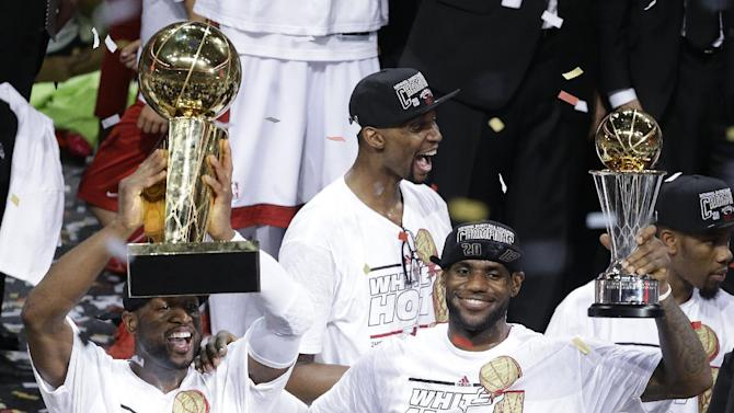 In this June 21, 2013 file photo, the Miami Heat's Dwyane Wade, left, holds the Larry O'Brien NBA Championship Trophy as  LeBron James holds his Bill Russell NBA Finals Most Valuable Player Award after Game 7 of the NBA basketball championship against the San Antonio Spurs, in Miami. The Heat's Chris Bosh celebrates in the background. A person familiar with the situation tells The Associated Press that James has decided to opt out of the final two years of his contract with the Heat and become a free agent on July 1. Opting out does not mean James has decided to leave the Heat, said the person, who spoke on condition of anonymity because neither the four-time NBA MVP nor the team had made any public announcement