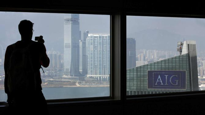 File photo of a man taking pictures of AIG Tower in Hong Kong