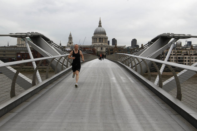 A man runs along an almost deserted Millennium Bridge, with St Paul's Cathedral in the background centre, in central London, Wednesday, Aug. 1, 2012. People are heeding government advice and staying away from central London during the London 2012 Olympics. (AP Photo/Sang Tan)