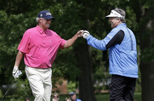 Kenny Perry, right, is congratulated by Russ Cochran after hitting a shot out of a bunker and into the fourth hole for eagle during the third round of the Senior PGA Championship golf tournament at Be