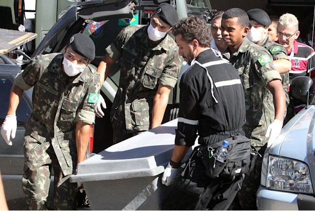 Brazil's soldiers carry a container with the remains of a victim outside a gymnasium where bodies were brought for identification in Santa Maria city, Rio Grande do Sul state, Brazil, Sunday, Jan. 27,