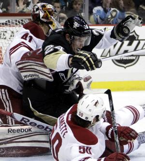 Pittsburgh Penguins' Matt Cooke (24) collides with Phoenix Coyotes goalie Mike Smith (41) after colliding with Coyotes' Antoine Vermette (50) in the second period of an NHL hockey game in Pittsburgh, Monday, March 5, 2012. (AP Photo/Gene J. Puskar)