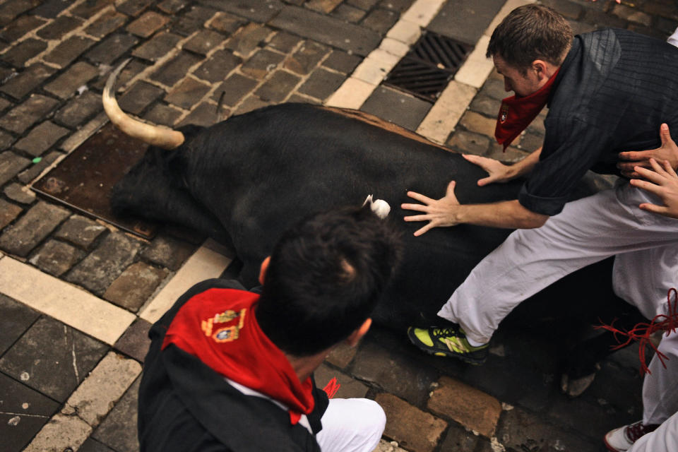 Revelers and a Cebada Gago's ranch fighting bull fall during the running of the bulls of the San Fermin festival, in Pamplona, Spain, Monday, July 9, 2012.(AP Photo/Daniel Ochoa de Olza)